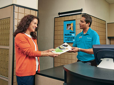 Associate showing female customer printed newsletter