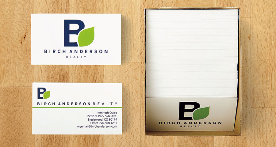 Box of double-sided business cards, with one sample displayed on a desk