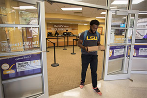 Student holding package walking out of store at LSU